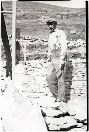 Working man constructing a stone wall. Photographer Tomás Ó Muircheartaigh.